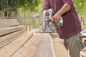 Mann sägt Holzbretter